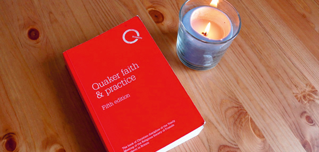 A wooden table top with a book with a red cover and a lit candle
